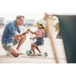 Dziewczynka siedzi na niebieskiej hulajnodze obok klęczy tata