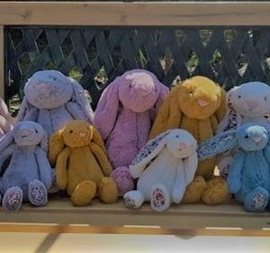Kolorowe króliczki Jellycat siedzą na ławce